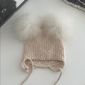 knitted girl's hat with buboes made of natural fur